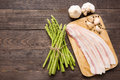 Smoked bacon with fresh asparagus on wooden background Royalty Free Stock Photo