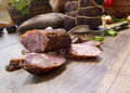 Smoked dried gammon ham and slices of sausages with bread, tomatos, herbs, garlic and basketson wooden board Royalty Free Stock Photo