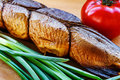 Smoked fish on cutting board with tomato and green onion closeup Royalty Free Stock Photo
