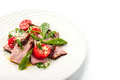 Smoked ham and arugula salad on the white background Royalty Free Stock Photo