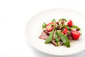 Smoked ham and arugula salad on the white plate horizontal Royalty Free Stock Photo