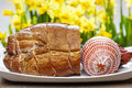 Smoked ham on wooden table yellow daffodils in the background Stock Photo