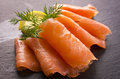 Smoked salmon as closeup on a black slate Royalty Free Stock Photos