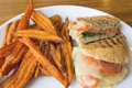 Smoked salmon panini closeup spinach tomato mozzarella cheese pesto mayo and sweet potato fries Stock Image