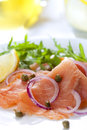 Smoked salmon salad with red onion capers lemon and arugula Stock Images
