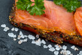 Smoked salmon slices and seasoning on natural black stone backgr