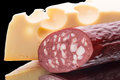 Smoked sausage maasdam cheese black background Royalty Free Stock Photo