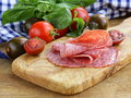 Smoked sausage tomatoes and basil on a wooden cutting board Stock Photos