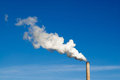 Smokestack and horizontal white smoke on blue sky. Royalty Free Stock Photo