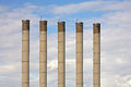 Smokestacks high against blue sky Stock Photo