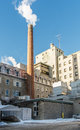 Smoking chimney smoke rising from the can pollute the environment on a nice blue sky Stock Photography