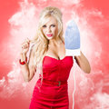 Smoking hot blond cleaning woman with red hot iron emotional holding scorching in a depiction of housework smoke background Royalty Free Stock Photo