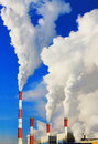 Smoking pipes of thermal power plant against blue sky Royalty Free Stock Photo