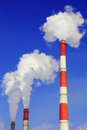 Smoking pipes of thermal power station plant against blue sky Stock Images