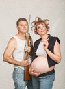 Smoking pregnant female hillbilly negligent couple with rifle and cigarettes Stock Photography