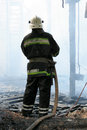 Smoldering remains ghetto house fireman spraying water firefighters extinguish fire apartment house Stock Image