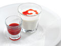 Smooth and creamy panna cotta with strawberry sauce raspberry in a small glass isolated on white Stock Photo