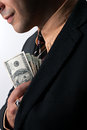 Smooth criminal close up of a business mans hand hiding money in his suit jacket pocket Royalty Free Stock Photography