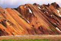 Smooth orange rhyolite mountains in landmannalaugar nature reserve in the hollows is last year s snow Stock Photography