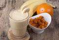 Smoothie of banana orange juice frozen sea buckthorn with y berries yogurt in a glass bananas oranges and in the Stock Images
