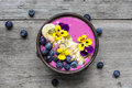 Smoothie bowl with chia seeds, blueberry, banana slices and flowers