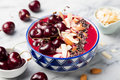 Smoothie bowl with fresh black cherries, coconut flakes, almond and cocoa nibs. Marble background