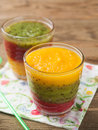 Smoothie glass of fresh peach kiwi and strawberry selective focus Royalty Free Stock Image