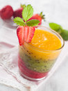 Smoothie glass of fresh peach kiwi and strawberry selective focus Stock Image