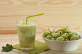 Smoothie from gooseberries in a glass and gooseberries in bowl on wooden table Stock Image