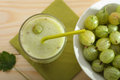 Smoothie from gooseberries in a glass and gooseberries in bowl on wooden table Royalty Free Stock Image