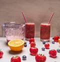 Smoothie of strawberries berries in glass jars with beautiful tubes on a white wooden table around the expanded fresh strawbe and Stock Images