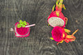 Smoothies of a red organic dragon fruit on an old wooden background