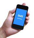 Sms sending text on phone screen in hand with white background Royalty Free Stock Photos