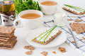 Snack with fresh tea and rye crispy bread Swedish crackers with cottage cheese, decorated with thin green onion, on white backgr