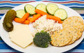 Snack plate of chicken salad cheese crackers and vegetables a snacks with broccoli carrots sliced cucumbers a pickle Royalty Free Stock Photos