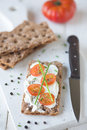 Snack time rye cracker with cream cheese sliced tomato served on a chopping board shallow dof Royalty Free Stock Photo