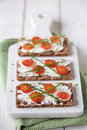 Snack time rye crackers with cream cheese sliced tomato served on a chopping board shallow dof Royalty Free Stock Images