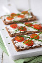 Snack time rye crackers with cream cheese sliced tomato served on a chopping board shallow dof Stock Photo