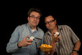 Snacks and games two guys playing with a retro video game while tucking into Royalty Free Stock Photography