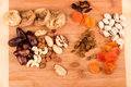 Snacks of nuts and dried fruits on a wooden surface Royalty Free Stock Photos