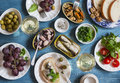 Snacks table - canned sardines, mussels, octopus, grape, olives, tomato and two glasses white wine on wooden table, top view. Royalty Free Stock Photo