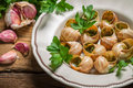 Snails baked in garlic butter and served with parsley on old wooden table Royalty Free Stock Image