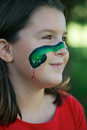 Snake face painting young girl with green on her cheek Royalty Free Stock Image