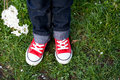 Sneakers on childs feet flower in hand Stock Photos
