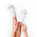 Sneakers on women legs white background Stock Image