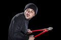 Sneaky burglar a wearing black clothes holding huge wire cutters over black background Royalty Free Stock Images