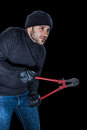 Sneaky saboteur a burglar wearing black clothes holding huge wire cutters over black background Royalty Free Stock Images