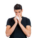 Sneezing closeup portrait sick young man student worker with allergy or germs cold blowing his nose with kleenex looking miserable Stock Photography