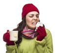 Sneezing mixed race woman drinks hot tea while blowing nose sick wearing winter hat and gloves her sore and holding cup of Royalty Free Stock Photography