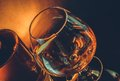 Snifter of brandy in elegant typical cognac glass near near bottle on black table, warm tint style Royalty Free Stock Photo